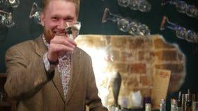 有红色胡子的可爱的人在与软的内景照明的一个酒吧喝着鸡尾酒,与某人谈话并且笑 股票视频