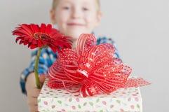 有红色花和礼物盒的小男孩 免版税库存照片