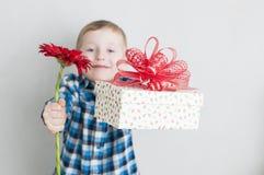 有红色花和礼物盒的小男孩 免版税库存图片