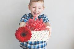 有红色花和礼物盒的小男孩 库存图片