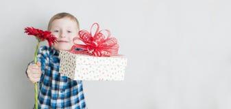 有红色花和礼物盒的小男孩 图库摄影