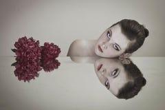 有红色花的女孩在镜子附近 库存照片