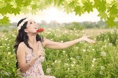有红色花的愉快的女孩 库存照片