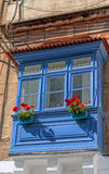 有红色花的蓝色阳台 库存图片