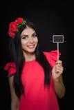 有红色花花圈的美丽的妇女拿着一块木匾 免版税库存照片