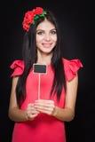 有红色花花圈的美丽的妇女拿着一块木匾 免版税库存图片