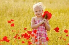 有红色花花束的美丽的小女孩  免版税库存照片