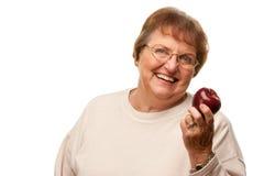 有红色苹果计算机的可爱的资深妇女 库存图片