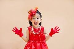 有红色葡萄酒服装的逗人喜爱的亚裔女孩 免版税图库摄影