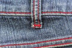 有红色螺纹的牛仔裤 免版税库存照片