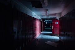 有红色衣物柜和门的-葡萄酒,被放弃的学校走廊 库存图片