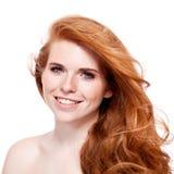 有红色被隔绝的头发和雀斑的美丽的年轻微笑的妇女 免版税库存照片