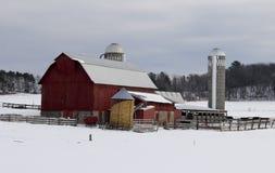 有红色谷仓的家庭农场在多雪的冬天背景中 免版税库存照片