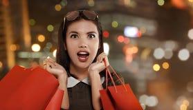 有红色购物袋的愉快的亚裔妇女庆祝黑星期五的 图库摄影