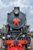 有红色轮子的蒸汽机车 在路轨的减速火箭的机车 黑色机车 库存图片