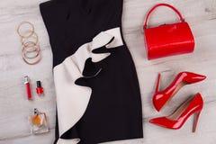 有红色辅助部件和化妆用品的黑白礼服 库存图片