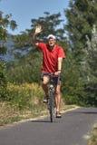 有红色运动服的年轻人在从匈牙利的自行车路 免版税库存图片