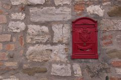 有红色邮箱的石墙 库存照片