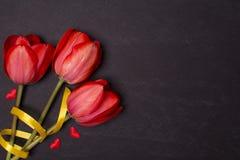 有红色郁金香和心脏的空的干净的黑黑板 顶视图 库存图片
