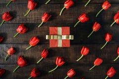 有红色郁金香的红色礼物盒在黑暗的木背景 免版税图库摄影