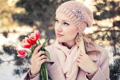 有红色郁金香的美丽的白肤金发的妇女 春天室外画象 免版税库存照片