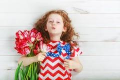 有红色郁金香的逗人喜爱的小女孩在庆祝7月4日 Indepe 免版税库存图片