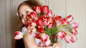 有红色郁金香花束的愉快的女婴  孩子嗅郁金香的气味 生日和母亲节的概念 股票录像