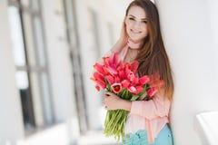 有红色郁金香花束的美丽的妇女  免版税库存图片