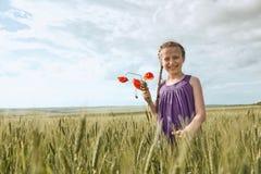 有红色郁金香花的摆在麦田的,明亮的太阳,美好的夏天风景女孩 库存图片