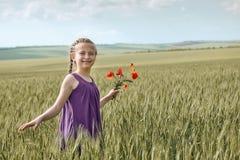 有红色郁金香花的摆在麦田的,明亮的太阳,美好的夏天风景女孩 免版税库存图片
