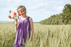 有红色郁金香花的摆在麦田的,明亮的太阳,美好的夏天风景女孩 免版税库存照片