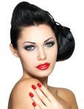 有红色钉子和方式构成的美丽的妇女 免版税库存图片