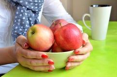 有红色钉子的女孩在她的手指拿着绿色碗有很多苹果 免版税图库摄影