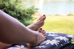 有红色钉子脚的妇女腿在轻便折叠躺椅,假期概念放置 免版税库存图片