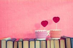 有红色钩针编织心脏的两个杯子在书 库存照片