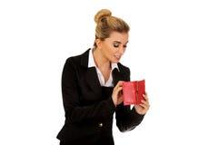 有红色钱包的愉快的微笑的女实业家 免版税库存图片