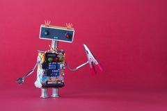 有红色钳子的友好的机器人杂物工玩具 桃红色背景拷贝空间 库存图片