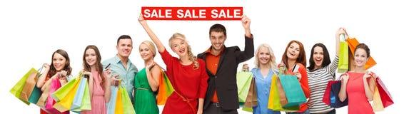 有红色销售标志和购物袋的愉快的人 免版税图库摄影
