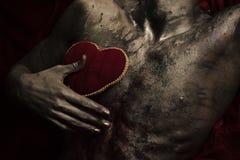 有红色长毛绒软的心脏玩具的,黑暗的背景裸体躯干 库存照片