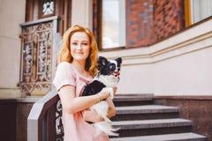 有红色长的头发的一个美丽的少妇拿着两朵花一条小,逗人喜爱的滑稽的大眼狗, Th一只黑白宠物  免版税图库摄影