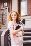 有红色长的头发的一个美丽的少妇拿着两朵花一条小,逗人喜爱的滑稽的大眼狗, Th一只黑白宠物  库存图片