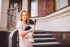 有红色长的头发的一个美丽的少妇拿着两朵花一条小,逗人喜爱的滑稽的大眼狗, Th一只黑白宠物  库存照片