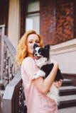 有红色长的头发的一个美丽的少妇拿着两朵花一条小,逗人喜爱的滑稽的大眼狗, Th一只黑白宠物  免版税库存图片