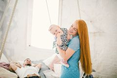 有红色长的头发的年轻美丽的妇女在一件蓝色礼服在说谎上午的床附近抱在她的手上的一个孩子一个年金发碧眼的女人 库存图片