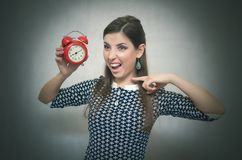 有红色闹钟的恼怒的妇女 睡过头 后在工作或学校教训 免版税库存照片
