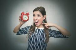 有红色闹钟的恼怒的妇女 睡过头 后在工作或学校教训 库存图片