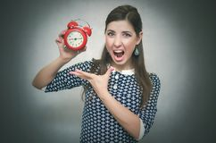 有红色闹钟的恼怒的妇女 睡过头 后在工作或学校教训 免版税库存图片