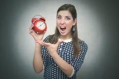 有红色闹钟的恼怒的妇女 睡过头 后在工作或学校教训 库存照片