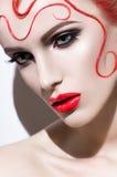 有红色面孔艺术的妇女 库存图片