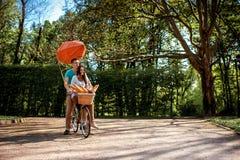有红色飞船和ba的可爱的年轻夫妇骑马自行车 库存图片